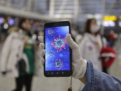 Homem mostra ilustração do coronavírus, responsável pelo surto que preocupa autoridades chinesas.