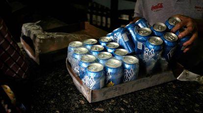 Um trabalhador com uma caixa de cervejas Polar.