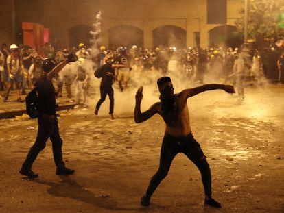 Um manifestante joga pedras contra a polícia antidistúrbios libanesa, em Beirute. Em vídeo, nova jornada de confrontos em Beirute.