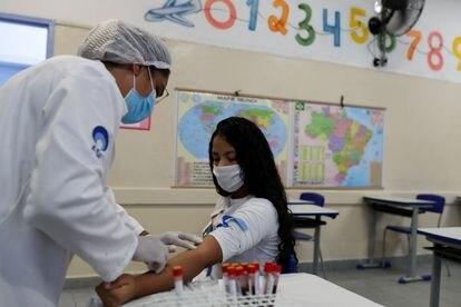 Enfermeira tira amostra de sangue de estudante em São Paulo para teste de coronavírus.
