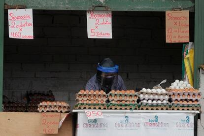 Uma mulher se protege da covid-19 na banca onde vende ovos, em Quito (Equador).