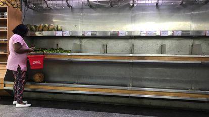 Mulher seleciona limões em um supermercado em Caracas.