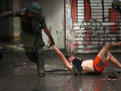 Policiais arrastam a manifestante durante um protesto na segunda-feira em Santiago.