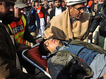 Ferido é socorrido após ataque no Paquistão.