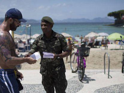 Soldado distribui material informativo sobre o zika em Copacabana.