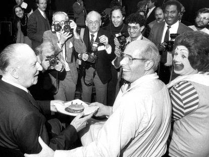 Foto tirada em 1984. O então presidente do McDonald's, Ed Rensi (centro), preparou para Richard McDonald (esquerda) o hambúrguer que levou a rede à marca de 50 milhões de sanduíches. O palhaço Ronald McDonald também participa da comemoração.