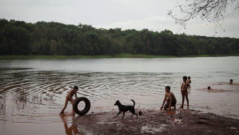 Crianças nadam no rio Paraná. A administração de Itaipu proibiu a comunidade de pescar na represa.