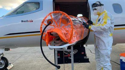 Profissional da saúde prepara maca especial para transporte de paciente com covid-19 em UTI aérea em meio à pandemia no Brasil.