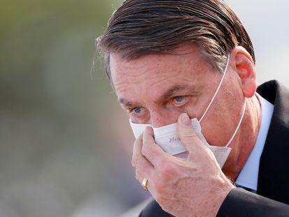 Jair Bolsonaro com a mão em sua máscara durante ato no Palácio do Planalto, em 9 de junho.