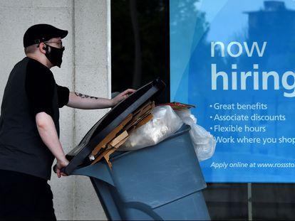 Homem com máscara caminha diante de uma loja que anuncia vagas de trabalho, no Estado da Virgínia.