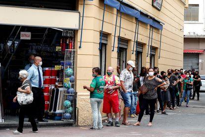Clientes fazem fila para entrar em loja do centro de São Paulo após abertura do comércio de rua ser autorizada em determinados horários.