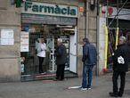 Una farmacéutica entrega los medicamentos a una clienta desde la puerta del establecimiento.