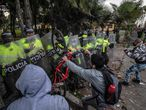 Demonstrators clash with riot police during a protest against the death of a lawyer under police custody, in Bogota on September 9, 2020. - A man died after being detained by police officers on September 9 in Bogota and receiving repeated electric shocks with a stun gun while immobilized by police on the ground. (Photo by Juan BARRETO / AFP)