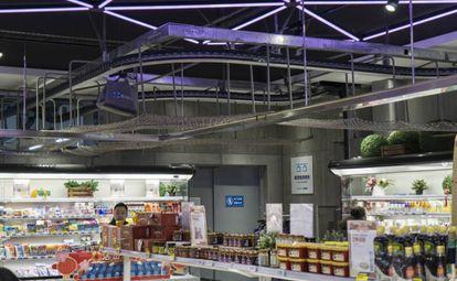 Alguns produtos são transportados pelo teto da loja. São artigos destinados ao comércio eletrônico, que vão para um depósito, onde uma moto elétrica os aguarda para entrega
