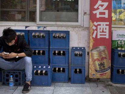 Trabalhador ao lado de caixas de cerveja em Pequim, China, um dos mercados onde a nova empresa poderá enfrentar problemas regulatórios.