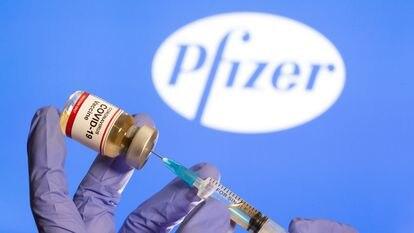 """Uma mulher segura um pequeno frasco com o rótulo """"Vacina COVID-19"""" e uma seringa médica na frente do logotipo da Pfizer."""