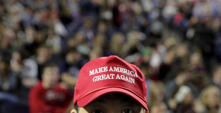 Um partidário de Trump com um boné com seu lema