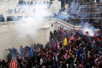 Agentes da polícia jogam gases lacrimogêneos para dispersar os seguidores de Trump durante a invasão do Capitólio.
