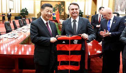 Bolsonaro presenteia o presidente chinês Xi Jinping com uma jaqueta do Flamengo em encontro em Pequim em 2019.