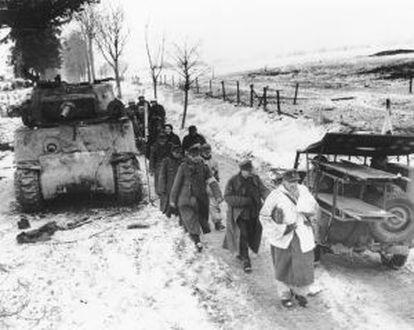 Presos alemães passam por um Sherman e um jeep Willys durante a batalha das Ardenas.