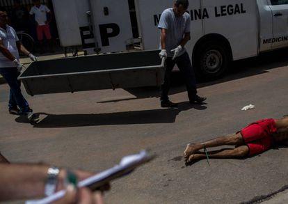 Policiais recolhem o corpo de um homem assassinado num sábado de abril em Natal (RN).