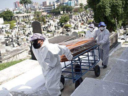 Funcionários de cemitério em Nova Iguaçu carregam caixão de uma vítima da covid-19.