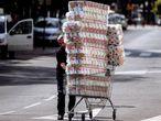 Un reponedor lleva un carro con papel higiénico a un comercio en Málaga.