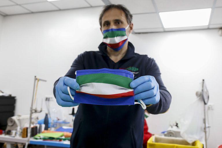 Fabricante mostra máscara de pano feita com as cores da bandeira da Itália, em Roma.