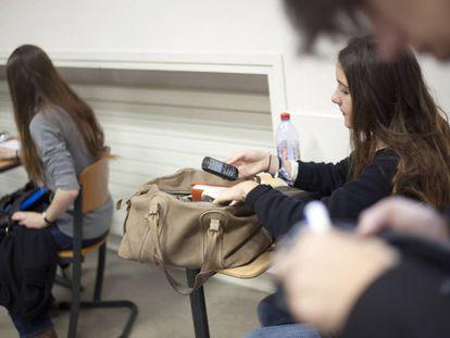 Garota francesa consulta seu celular na sala de aula.