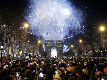 Centenas de pessoas tiram fotografias dos fogos de artifício sobre o Arco do Triunfo na celebração de Ano Novo na Avenida Champs-Élysées em Paris, França.