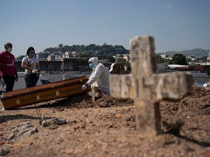 Rodrigo Bessa, à esquerda, no enterro da mãe, Edenir, suspeita de ter contraído coronavírus, no Rio.