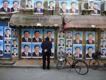 Transeunte observa cartazes com a imagem do presidente Xi Jinping, em Xangai.