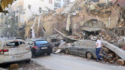 Uma mulher caminha nesta quarta-feira junto a edifícios e veículos danificados pela explosão da véspera em Beirute.