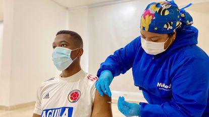 Fotografia cedida pela prefeitura de Barranquilla que mostra o jogador colombiano Carlos Cuesta recebendo a vacina.