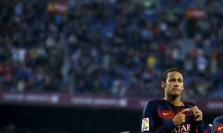 Neymar aponta para o escudo do Barcelona.