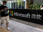 A man looks at his smartphone as he walks by the Microsoft office in Beijing, China on Friday, Aug. 7, 2020. The Biden administration on Monday, July 19, 2021 blamed China for a hack of Microsoft Exchange email server software that compromised tens of thousands of computers around the world earlier this year. (AP Photo/Ng Han Guan)
