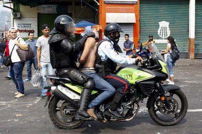 Policiais prendem um manifestante em San Cristóbal em março.