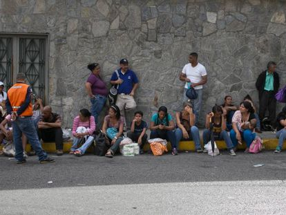 Um grupo de venezuelanos faz fila em frente a um supermercado de Caracas.