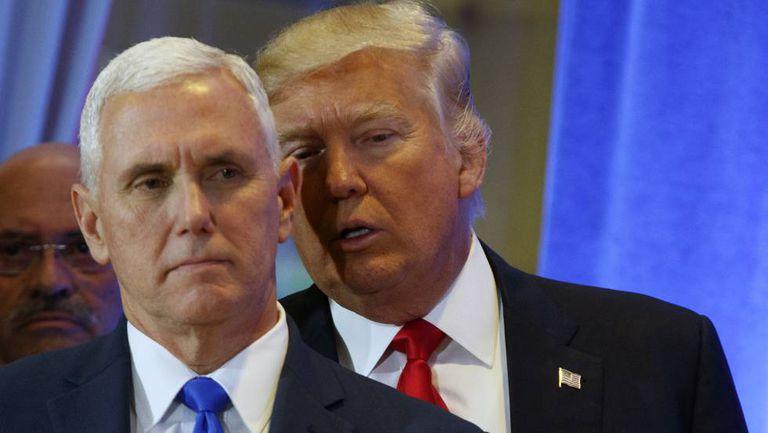 Donald Trump, em segundo plano, fala com Mike Pence.