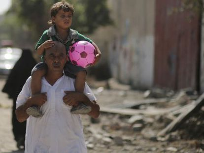Um palestino leva seu filho nos ombros em Gaza.