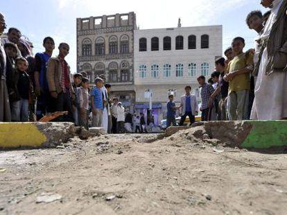 Curiosos no local da explosão de um artefato em Sanaa.
