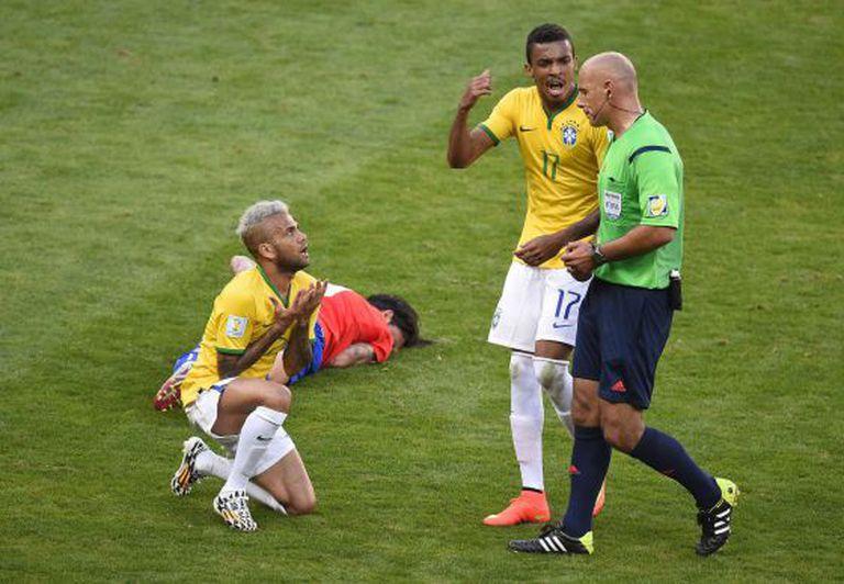 Daniel Alves se ajoelha para argumentar com Webb.