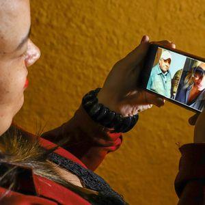 BELO HORIZONTE, MG, 05.08.2020 – Brasil se aproxima de 100 mil mortes por Covid-19. Na foto: A recepcionista Maíra Diniz Câmpara, que perdeu o pai Paulo Roberto Dias Câmpara, de 75 anos, e sua filha, Samira Diniz Câmpara, 40, vítimas de Covid-19. Maíra segura celular com fotos do pai e da irmã. (Foto: Flávio Tavares/El País)