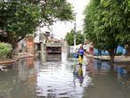 Maria das Graças de Andrade caminha pela rua Tite de Lemos, no Jardim Pantanal, nesta terça-feira. A via está alagada desde a chuva de domingo.
