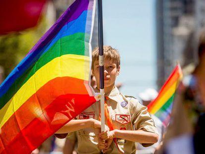 Escoteiro segura uma bandeira gay.