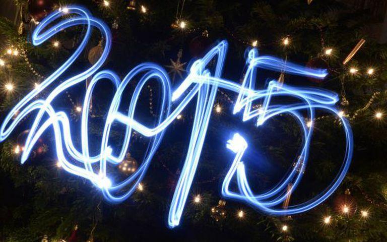 2015 escrito com lanternas de led em frente a árvore de Natal.