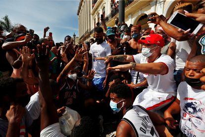 O cantor e compositor cubano Yomil (de boné vermelho), conversa com os manifestantes diante do Capitólio de Cuba, em Havana, em 11 de julho.