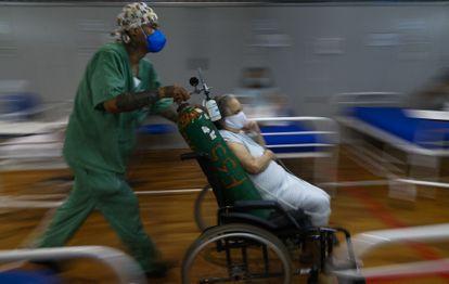Uma paciente com covid-19 é transportada em um hospital montado em um ginásio de esportes em Santo André, São Paulo.