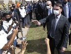 Wearing a protective face mask as a precaution against the new coronavirus, Brazil's President Jair Bolsonaro greets people after a ceremony to deliver affordable homes built by the government, in Brasilia, Brazil, Monday, April 5, 2021. In a television interview on Friday, April 23, 2021, Bolsonaro suggested that the army might be called into the streets to restore order if lockdown measures against COVID-19 that he opposes lead to chaos. (AP Photo/Eraldo Peres)