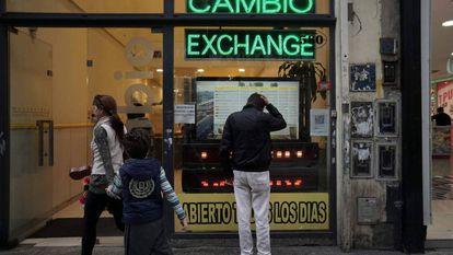 Transeunte olha tela com as cotações das moedas estrangeiras numa casa de câmbio no centro de Buenos Aires.